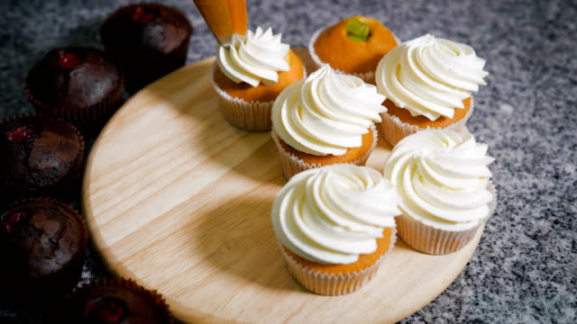 Confectioner decorated with vanilla cream freshly cooked muffins before you take them for sale. Masterpiece of culinary art on a wooden board in the kitchen video
