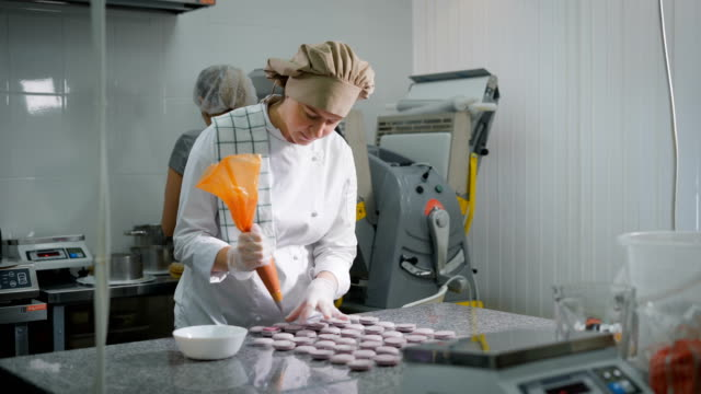 Confectioner pours custard on freshly baked cookies using pastry syringe. Girl in white uniform loves to bake sweet. Assistant cook prepares forms for cake on the background video