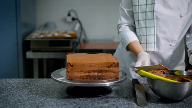 Confectioner with a spatula spread chocolate on a freshly baked cake on a professional kitchen in a bakery. Chef - cooker returns unused cream back into the metal bowl video