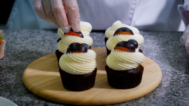 Confectionery. The girl is preparing for the holiday custom cupcakes. Muffins are ready on the table. Confectioner finishes execute chocolate cupcakes. Woman decorates cupcakes fruit video