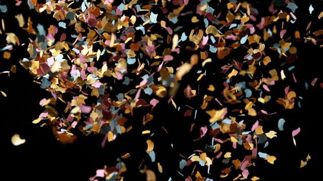 Confettis Falling against Black Background, Slow Motion 4K video