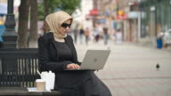Confident Arab businesswoman using laptop outdoors video