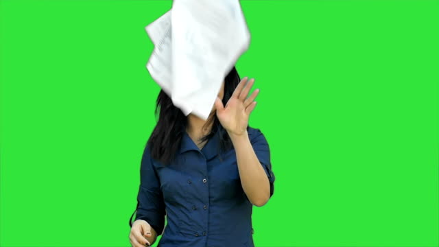 Confident asian businesswoman tearing the paper into small pieces and throwing it on a Green Screen, Chroma Key video