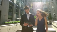 Confident business woman with a telephone and a businessman with a tablet walking near business center video
