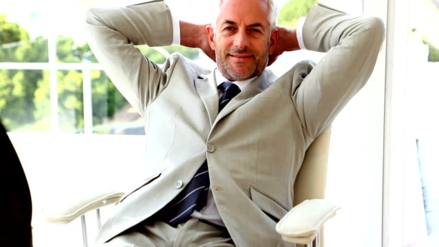 Confident businessman relaxing on his chair video
