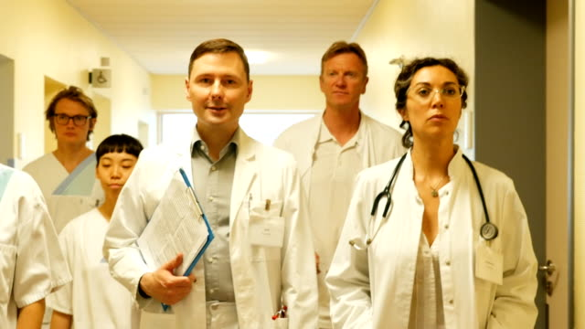 Confident doctors and nurses walking in corridor video