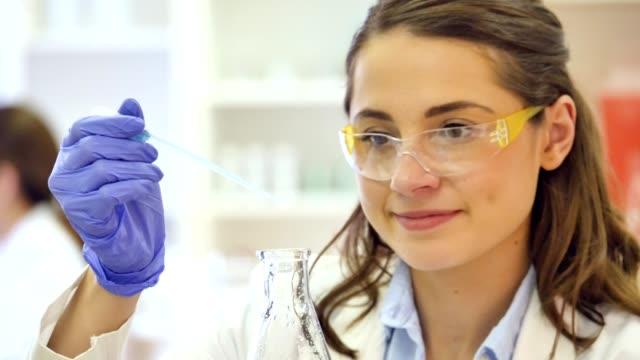 Confident female Caucasian scientist at work in research lab video