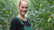 Confident female farmer in greenhouse video