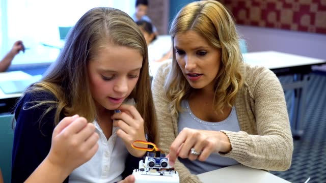 Confident female high school STEM teacher shows students how to program robot in technology class video