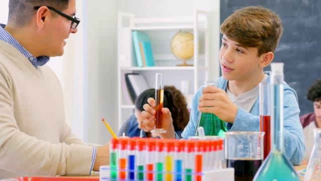 Confident Hispanic high school student and teacher in chemistry class video
