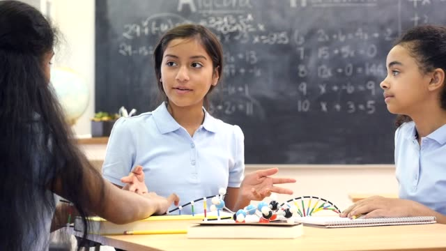 Confident Hispanic preteen girl leads chemistry project with classmates video