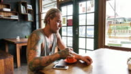 Confident man with tattoos drinking coffee video