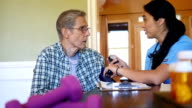 Confident mid adult Hispanic nurse checks senior patient's blood pressuring during home visit video