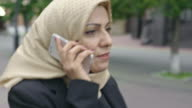Confident Middle Eastern woman talking on phone video