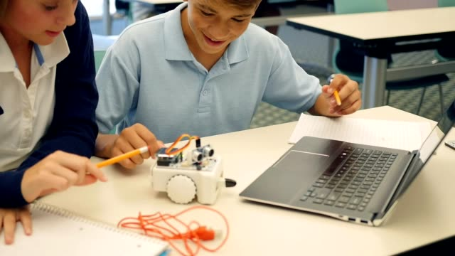 Confident private high school STEM students test robot in engineering class video