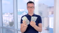 Confident, serious man counting and showing money, US dollars into camera video
