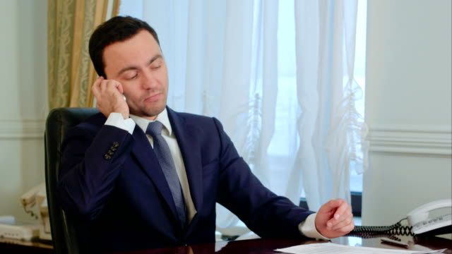 Confident young businessman takes a call in a modern office video