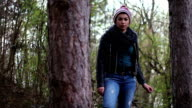 A confident young girl looking at camera in between trees in a woods video