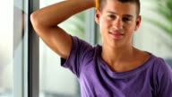 Confident young man standing at window video