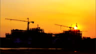 Construction cranes and building with sunset,Time lapse video