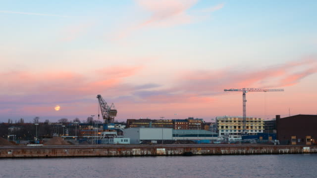 Construction cranes by the water at dusk. Industrial harbor district in Helsingborg, Sweden video