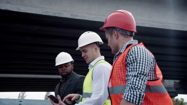 Construction engineers with supervisor near bridge video