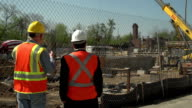 Construction foreman and business man look over worksite video
