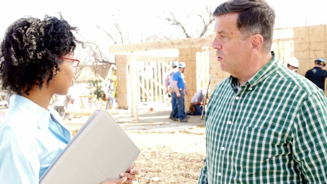Construction foreman greets executive at construction site video