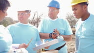 Construction foreman instructing volunteers as the build home for charity video