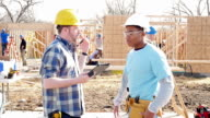 Construction foreman with digital table gives instructions to volunteer as they build home for charity video