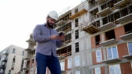 Construction manager browsing smartphone at building place. video