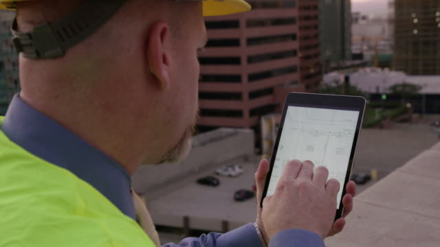 Construction manager looking at plans on touch screen video