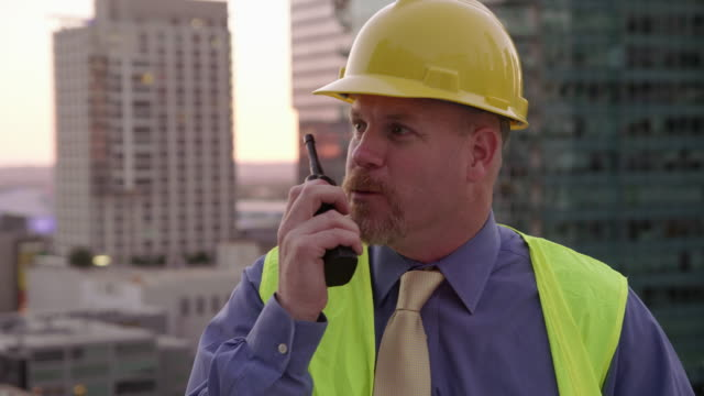 Construction manager on rooftop talking on walkie talkie video