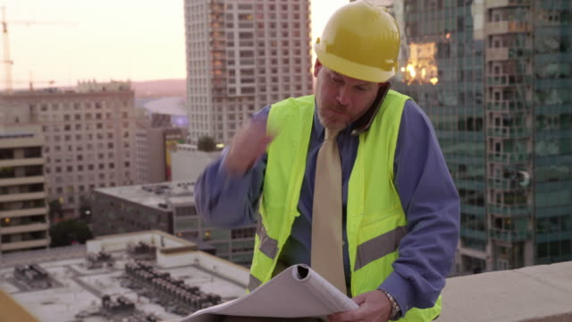 Construction manager on rooftop using looking at plans video