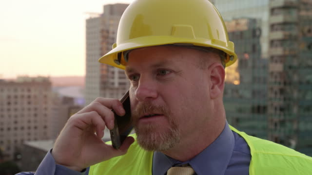 Construction manager on rooftop using phone video