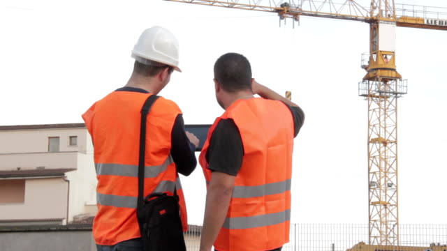 Construction people using electronic tablet on site video