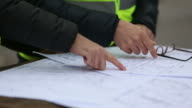 Construction personnel hands drawing on blueprints video