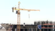 Construction site with a crane. New residential area building. High-altitude roof-top workers video