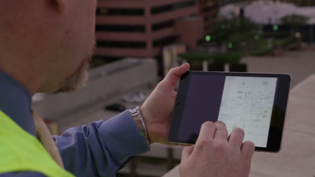 Construction supervisor looking at plans on tablet video