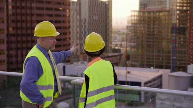 Construction supervisors look at city skyline from rooftop video