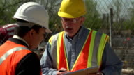 Construction worker and business man talking on site video
