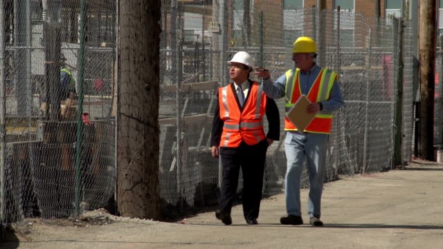 Construction worker and business man visiting worksite video