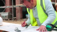 Construction Worker Checking Plans On Building Site video