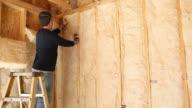 Construction Worker Insulating Wall with Fiberglass Batt video