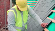 Construction Worker On Building Site Laying Slate Tiles video