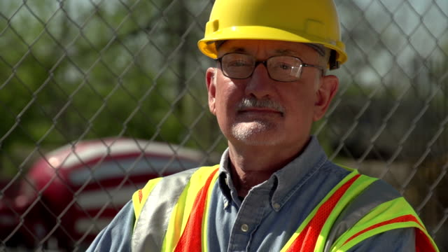 Construction worker on site, looking at camera, close up video