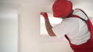 Construction worker sanding a drywall. video