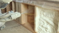 Construction Worker Spraying Expandable Foam Insulation Between Wall Studs video
