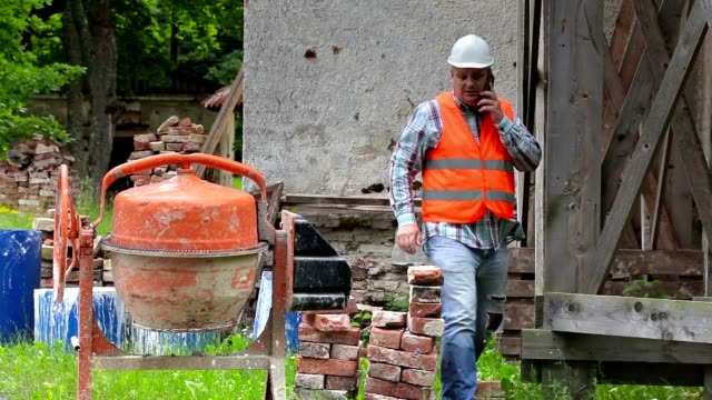 Construction worker talking on phone near wooden scaffolding and concrete mixer video