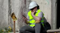 Construction worker thinking and using tablet PC near wall video